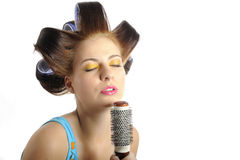 Young beautiful woman singing to brush microphone Stock Image