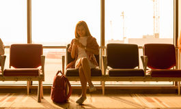 Young beautiful woman sit in airport with travel bag use smartph. One with ear phone at airport wait for flight, world exploration concept Stock Image