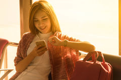 Young beautiful woman sit in airport with travel bag use smartph. One with ear phone at airport wait for flight, world exploration concept Royalty Free Stock Photos