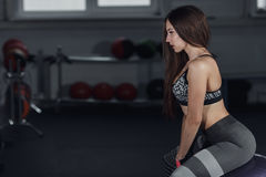Young beautiful woman sit on fitness ball in gym. Royalty Free Stock Images