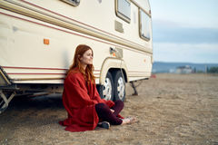 Young beautiful woman sits on the beach in a red plaid at the trailer Stock Photo