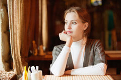 Young beautiful woman sits in cafe Stock Photos