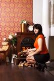 Young beautiful woman sits near the fireplace Stock Photo
