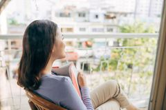 Young beautiful woman sits and reads a book on a terrace.  stock photography