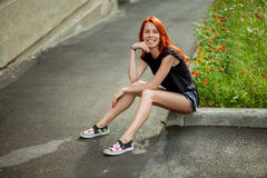 Young beautiful woman. Sits on rock border Stock Photos