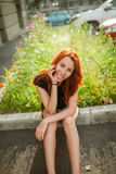 Young beautiful woman. Sits on rock border Royalty Free Stock Photo