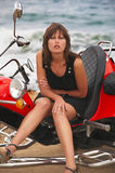 Young beautiful woman sits on trike. Near to the sea Stock Photography
