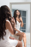 Young beautiful woman sitting against mirror Stock Images