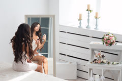 Young beautiful woman sitting against mirror Royalty Free Stock Photography