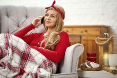 Young beautiful woman sitting in an armchair with a phone wrapped in a blanket during Christmas time stock photography