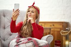 Young beautiful woman sitting in an armchair with a phone wrapped in a blanket during Christmas time stock image