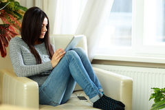 Young beautiful woman sitting on the armchair with tablet computer Stock Photos