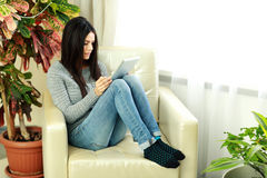 Young beautiful woman sitting on the armchair with tablet computer Royalty Free Stock Photography