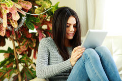 Young beautiful woman sitting on the armchair with tablet computer Royalty Free Stock Image