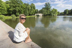 Young beautiful  woman sitting on the Bank of a green pond in the Park. Royalty Free Stock Photos