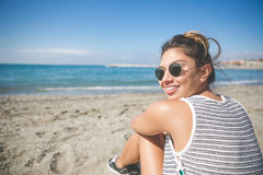 Young beautiful woman sitting on beach smiling. Back portrait of young beautiful woman sitting on beach smiling Royalty Free Stock Photo