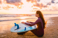 Young beautiful woman is sitting on the beach. Surf girl with surfboard on beach at sunset or sunrise. Surfer and ocean Stock Photo