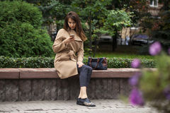 Young beautiful woman sitting on a bench in the autumn park Royalty Free Stock Photos