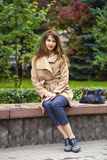Young beautiful woman sitting on a bench in the autumn park Stock Images