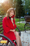 Young beautiful woman sitting on a bench in autumn Park Royalty Free Stock Photos