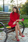 Young beautiful woman sitting on a bench in autumn Park Stock Photos