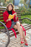 Young beautiful woman sitting on a bench in autumn Park Stock Images
