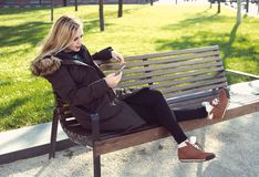 Young woman sitting on bench, autumn royalty free stock image