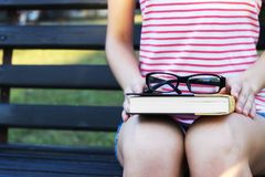 A young beautiful woman sitting on bench and reading book in the park. Pretty girl is outdoors on summer day Royalty Free Stock Photos