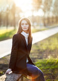 Young beautiful woman sitting on a bench in sun light on sunset. Time. Relax concept Royalty Free Stock Image