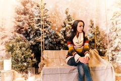 Young beautiful woman sitting on a bench or a swing in a snow-co Stock Photos