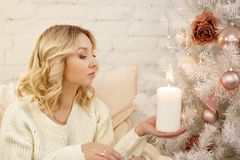 Young beautiful woman sitting with burning candles in their hands by the Christmas tree royalty free stock photo