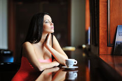 Young beautiful woman sitting in the cafe with a cup of coffee Stock Photos