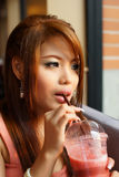 Young beautiful woman sitting in cafe holding and drinking a fruit smoothie through a straw. stock image