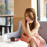 Young beautiful woman sitting in cafe and looking at her rose.  Stock Photography