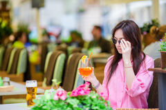 Young beautiful woman sitting in a cafe outdoor drinking tasty cocktail. Happy tourist enjoy european holidays at Stock Photography