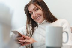 Young beautiful woman sits at a cafe table with phone stock image