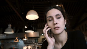 Young beautiful woman sitting in cafe and talking on mobile phone. Attractive female uses smartphone for work. stock video footage