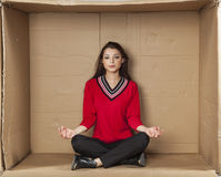 Young beautiful woman sitting in a cardboard box office Stock Image