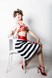 Young beautiful woman sitting on a chair, pin-up style, girl styling hair with curlers Stock Images