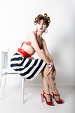 Young beautiful woman sitting on a chair, pin-up style, girl styling hair with curlers Royalty Free Stock Photography