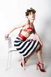 Young beautiful woman sitting on a chair, pin-up style, girl styling hair with curlers Stock Image