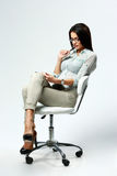 Young beautiful woman sitting on the chair and using table computer. On gray background Royalty Free Stock Photography