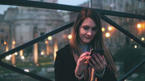 Young beautiful woman sitting in the city at evening and use smartphone. Girl texting with touchscreen keyboard. stock video