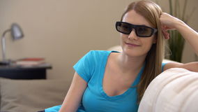 Young beautiful woman sitting on a couch in 3d-glasses. Switches on smart TV and watches 3d movie. stock video