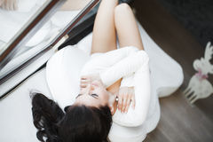 Young beautiful woman sitting on couch at her room Royalty Free Stock Photo