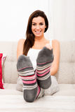 Young beautiful woman sitting on the couch Stock Photos