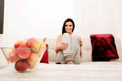 Young beautiful woman sitting on the couch Stock Images