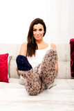 Young beautiful woman sitting on the couch Stock Photography