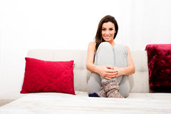 Young beautiful woman sitting on the couch Royalty Free Stock Photos