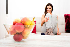 Young beautiful woman sitting on the couch Royalty Free Stock Photo